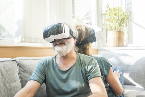 Happy mature couple sitting on couch at home wearing VR glasses - MOEF00937