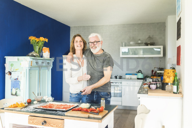 Happy mature couple embracing in kitchen at home - MOEF00940