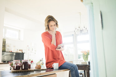 Woman with tablet and homemade strawberry jam at home - MOEF00943