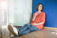 Relaxed woman sitting on the floor at home with healthy drink - MOEF00946