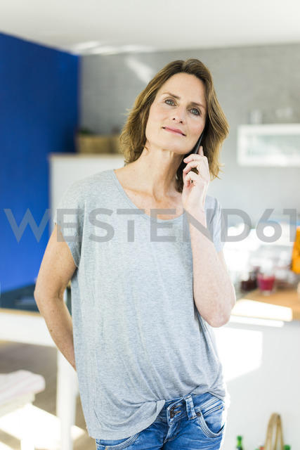 Portrait of woman on cell phone in kitchen at home - MOEF00949