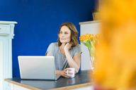 Thoughtful woman with laptop in kitchen at home - MOEF00955