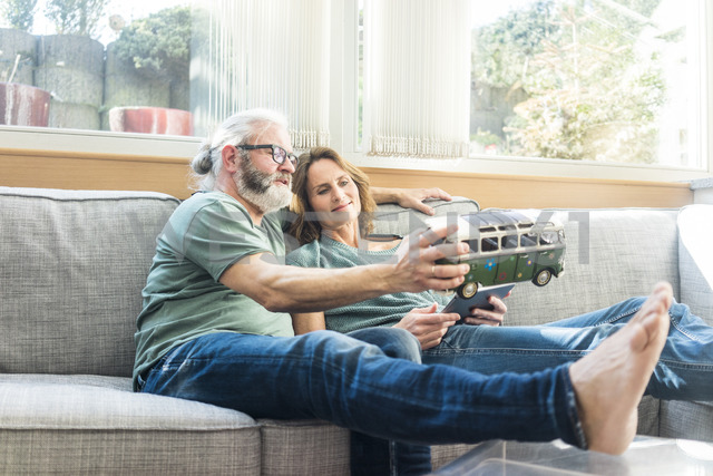 Mature couple on couch at home holding minibus model - MOEF00958