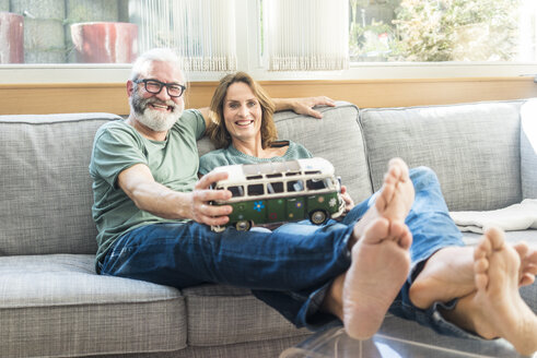 Happy mature couple on couch at home holding minibus model - MOEF00961