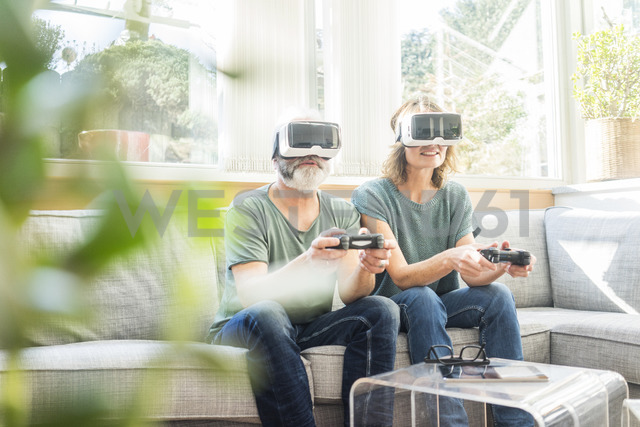 Mature couple sitting on couch at home wearing VR glasses playing video game - MOEF00967