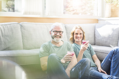 Happy mature couple with healthy drinks in living room at home - MOEF00973