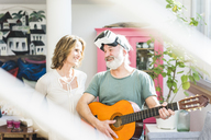 Happy mature couple with man playing guitar and wearing VR glasses - MOEF00976