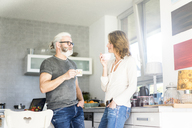 Mature couple drinking coffee in kitchen at home - MOEF00982