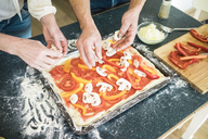 Close-up of couple preparing a pizza in kitchen at home - MOEF00985