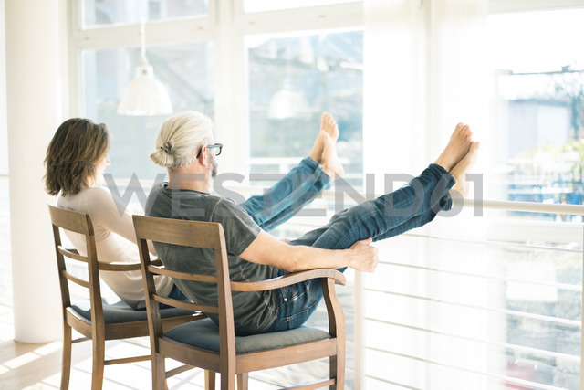 Relaxed mature couple sitting on chairs at home with feet up - MOEF00988