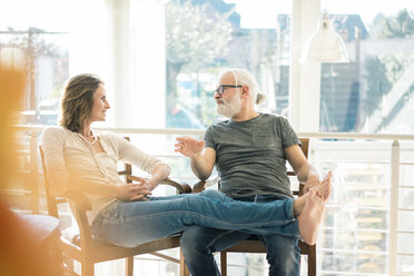 Relaxed mature couple talking on chairs at home - MOEF00991