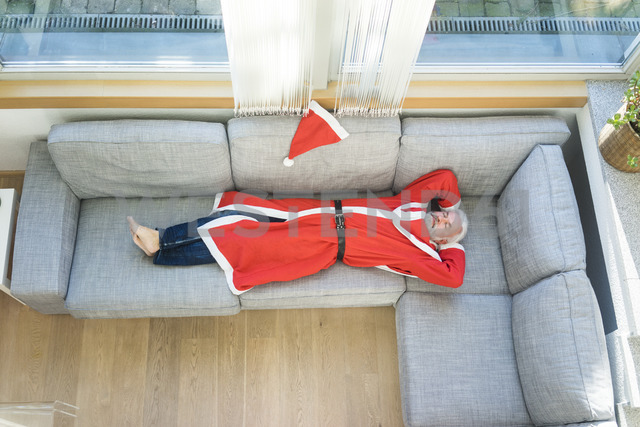 Bearded mature man wearing Santa costume lying on couch in living room - MOEF01000