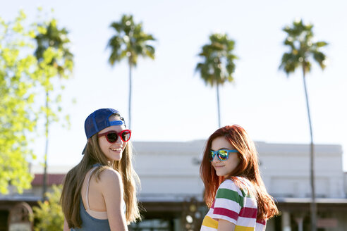 Portrait of happy female friends in sunglasses looking over shoulder - CAVF24894