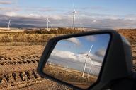 Windmills reflecting on side-view mirror of car at farm - CAVF24921