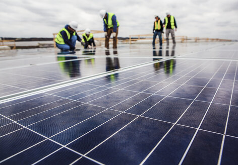 Workers working on solar panel field against cloudy sky - CAVF24975