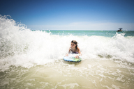 Girl surfing in sea against clear sky - CAVF25059