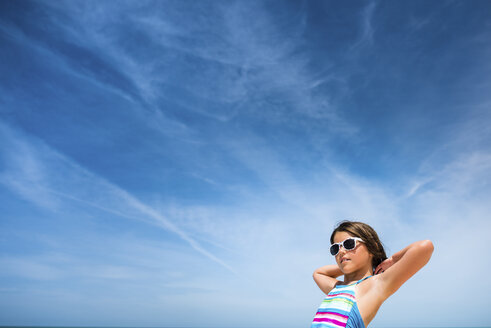 Low angle view of girl in sunglasses against cloudy sky - CAVF25062