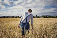 Rear view of female farmer walking on cultivated field - CAVF25134