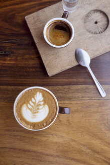 Overhead view of coffee cups on wooden table at cafe - CAVF25149