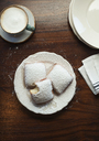 Overhead view of powdered sugar sprinkled on cookies served with coffee on table - CAVF25185
