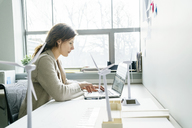 Side view of businesswoman using laptop computer while working in office - CAVF25218