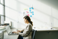 Side view of businesswoman using laptop while working by wind turbine models arranged on desk - CAVF25221
