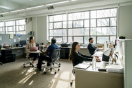 Business people discussing while sitting at desk in office - CAVF25224