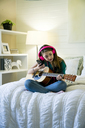 Teenage girl listening music through smart phone while sitting with guitar in bedroom - CAVF25326