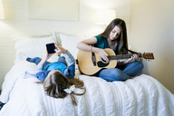 Girl using smart phone while sister playing guitar on bed at home - CAVF25329