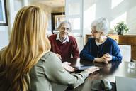 Financial advisor explaining plan to senior couple on tablet computer in office - CAVF25353