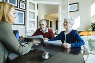 Senior couple holding documents while discussing with financial advisor in office - CAVF25362