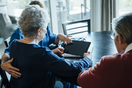 Home caregiver discussing over tablet computer with senior couple while sitting at dining table - CAVF25389