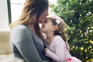 Close-up of mother kissing daughter by Christmas tree at home - CAVF25422