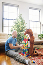 Father playing toy blocks with son dressed in costume at home - CAVF25428