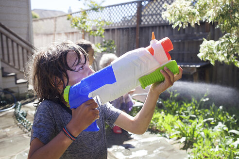 Grandmother and grandsons playing with squirt gun in yard - CAVF25479
