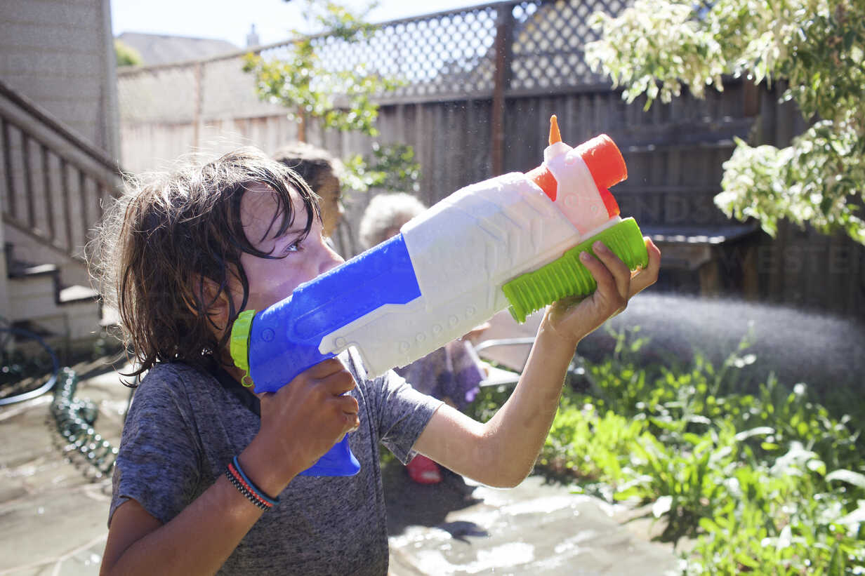 Grandmother and grandsons playing with squirt gun in yard - CAVF25479 - Cavan Images/Westend61