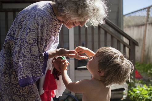Shirtless grandson giving toy to grandmother while standing in yard - CAVF25482