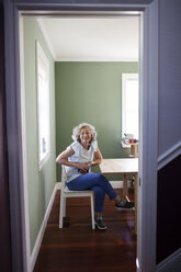 Portrait of confident senior woman sitting on chair at home seen through doorway - CAVF25485
