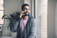 Smiling businessman talking on smart phone while sitting on window sill in office - CAVF25629