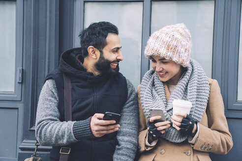 Happy man showing mobile phone to girlfriend while leaning by building - CAVF25638