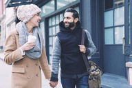 Happy couple holding hands while walking on footpath in city - CAVF25641
