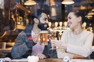 Happy couple toasting drinks seen through restaurant window - CAVF25644