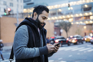 Man using mobile phone while standing on city street at dusk - CAVF25647