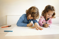 Siblings drawing at table in home - CAVF25656