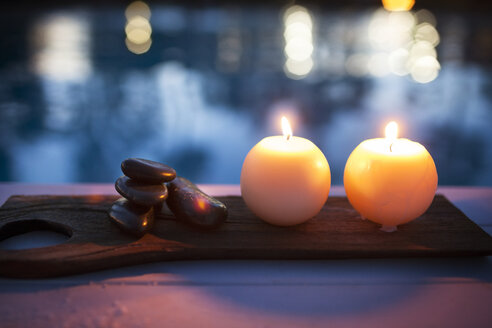 High angle view of illuminated candles and stones on table at health spa - CAVF25704