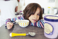 Portrait of cute boy leaning while having breakfast at home with mother in background - CAVF25713