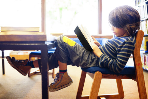 Full length side view of boy reading book in brightly lit library - CAVF25743