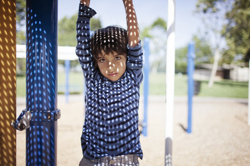 Portrait of boy hanging from outdoor play equipment at playground - CAVF25770