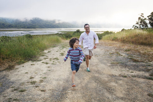 Cheerful father and son running on dirt road against cloudy sky - CAVF25779
