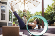 Woman playing with baby while doing yoga at backyard - CAVF25794